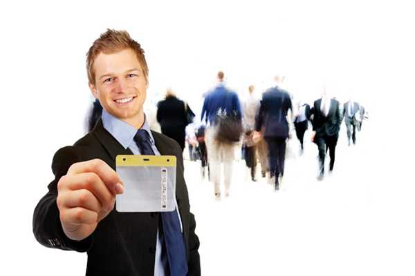 Young professional man wearing suit and tie holding up a Convention Strategy RFID Badge